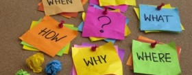 who, what, where, when, why, how questions - uncertrainty, brainstorming or decision making concept, colorful crumpled sticky notes on cork bulletin board
